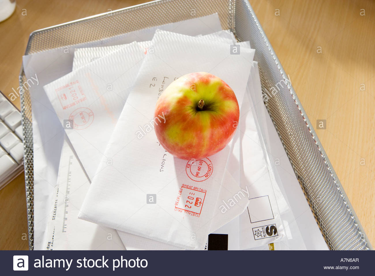 Apple and post in in tray on office desk close up elevated view still life - Stock Image