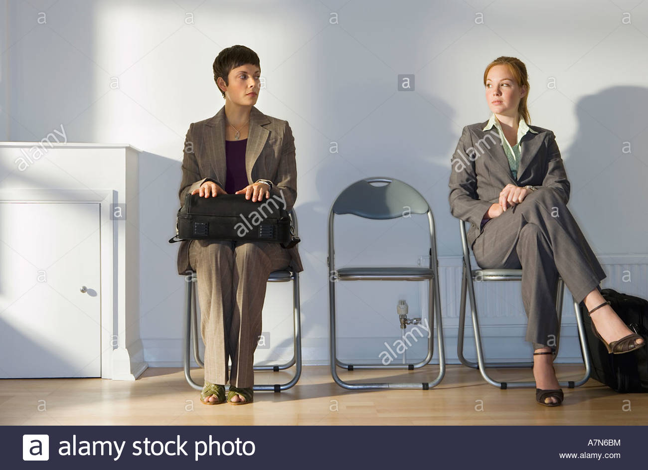 Two businesswomen sitting in office reception area waiting patiently front view - Stock Image