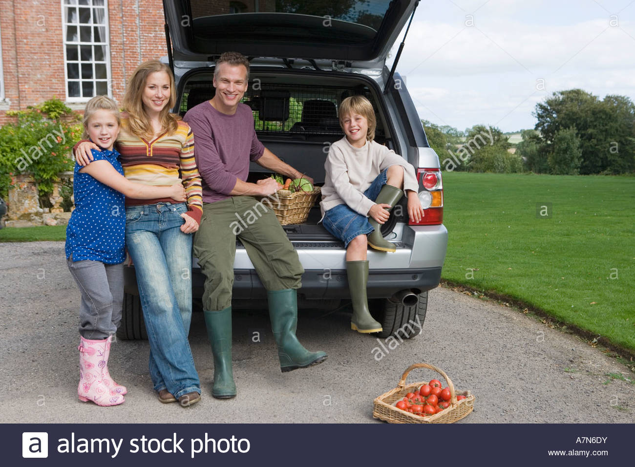 Family posing beside car boot with basket of vegetables in driveway smiling portrait - Stock Image