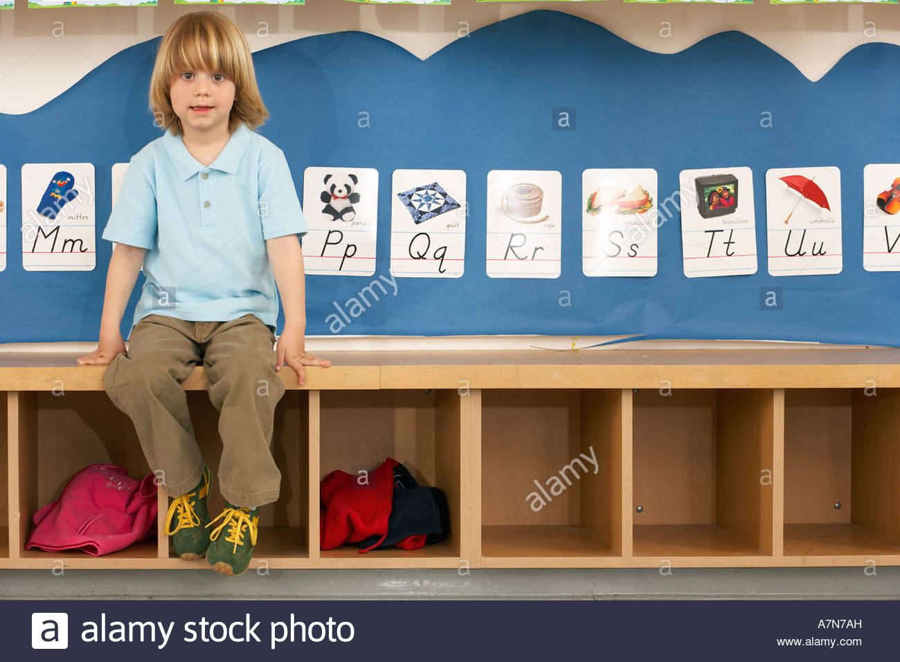 Blonde boy 4 6 sitting on bench in classroom front view portrait alphabet cards on wall - Stock Image