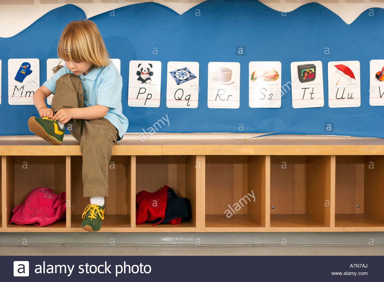 Blonde boy 4 6 sitting on bench in classroom tying shoelace alphabet cards on wall - Stock Image