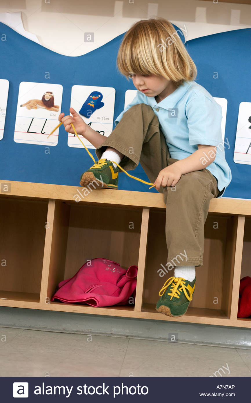 Blonde boy 4 6 sitting on bench in classroom tying shoelace alphabet cards on wall tilt - Stock Image