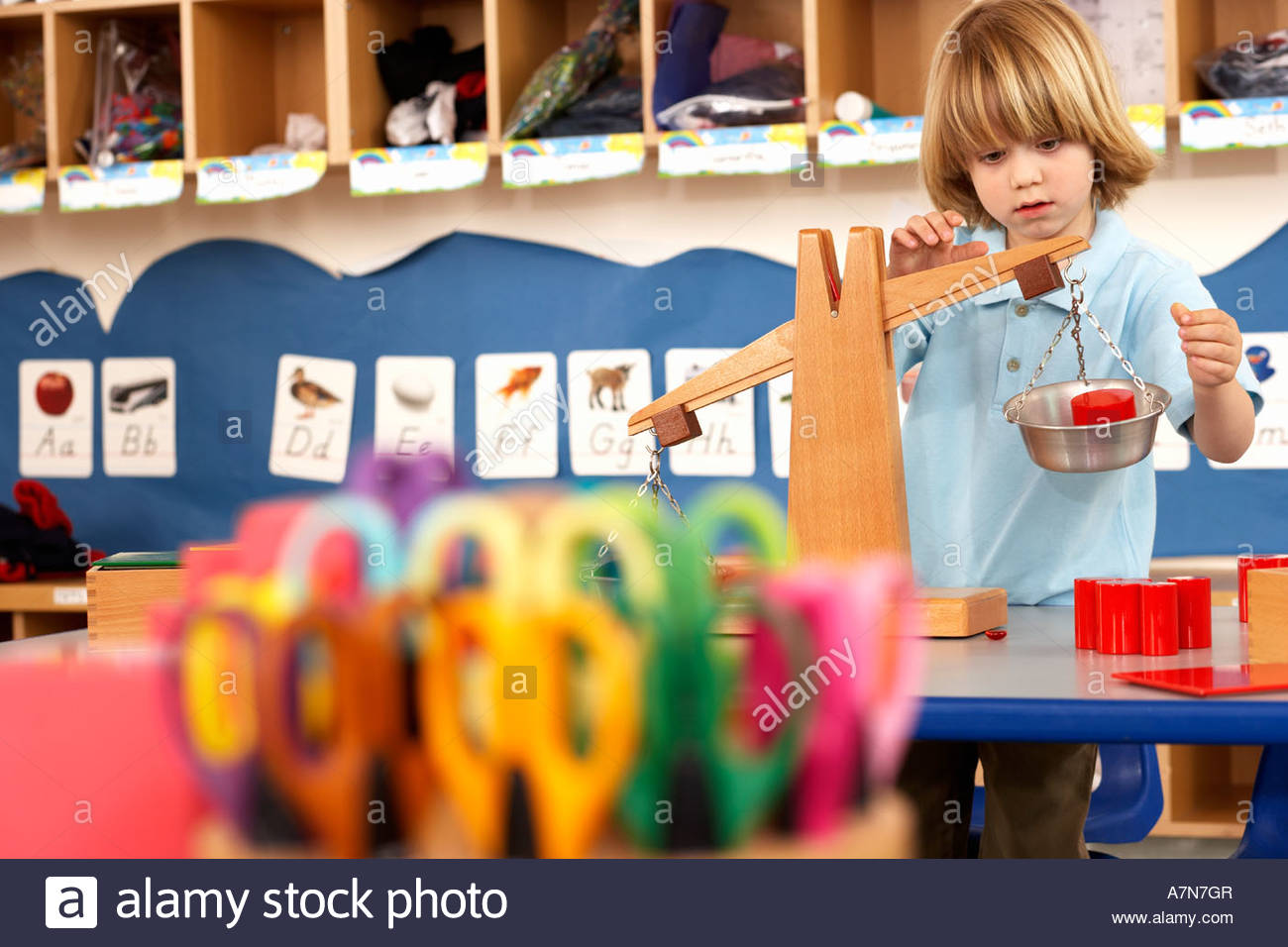 Multi coloured scissors in classroom focus on boy 4 6 playing with weight scale in background - Stock Image