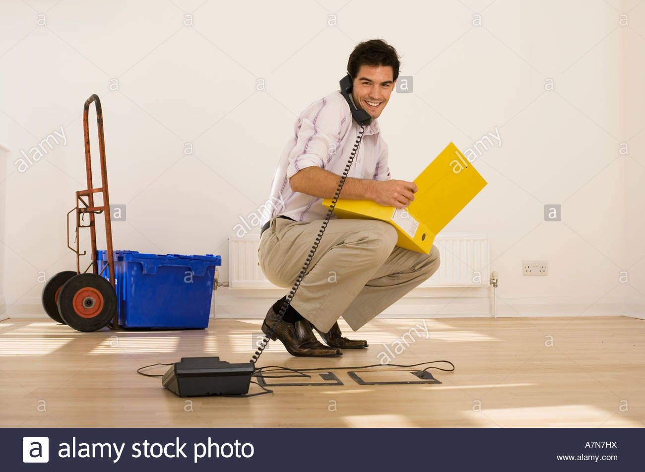Businessman crouching in office using telephone plugged into floor socket opening folder portrait - Stock Image