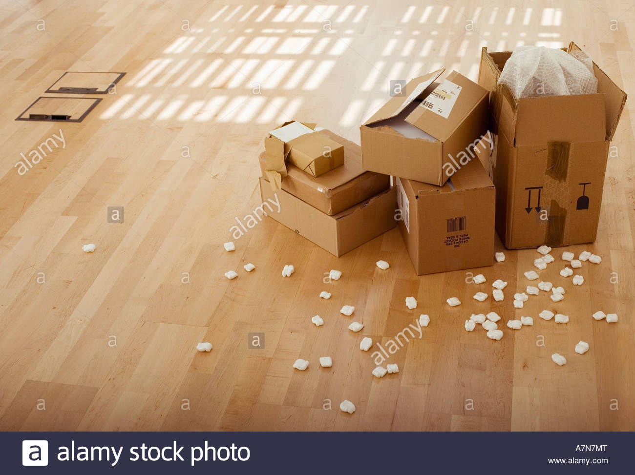 Stack of cardboard boxes beside packing foam on wooden floor