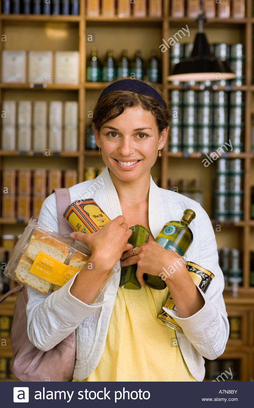 Female customer shopping in grocery store holding groceries smiling front view portrait - Stock Image