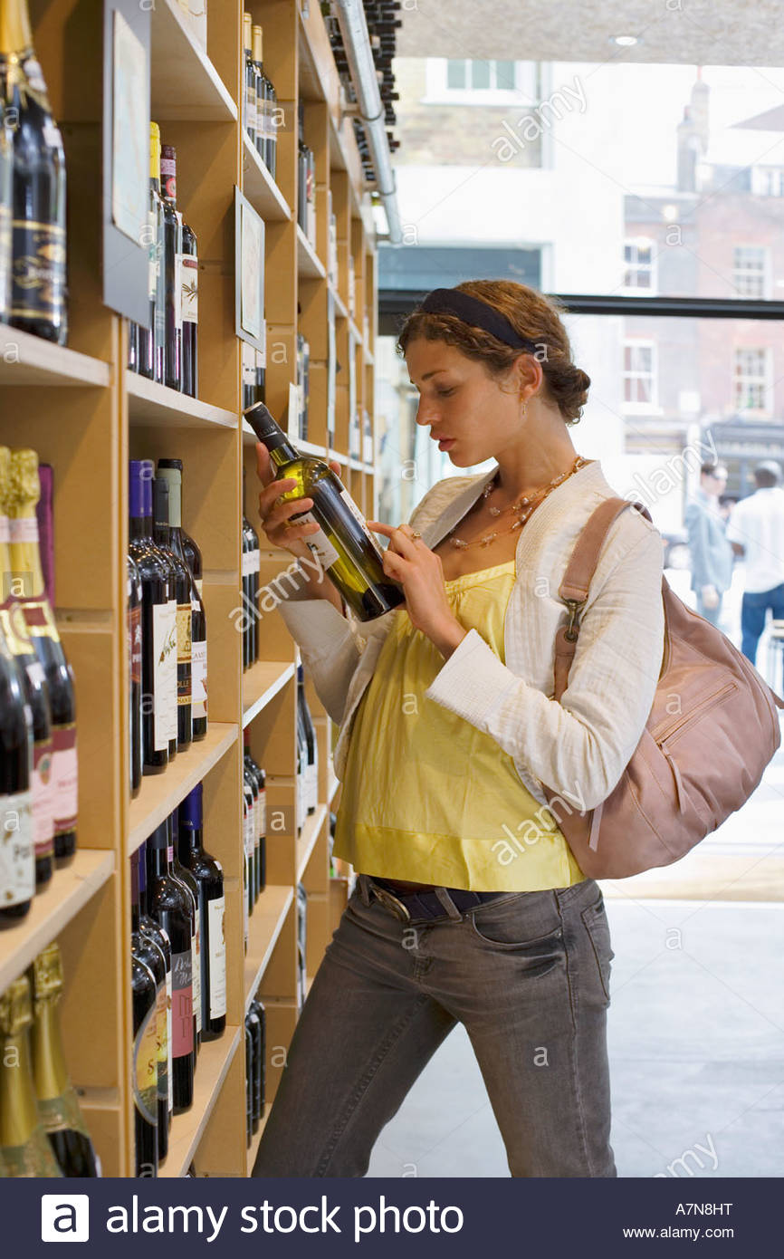 Female customer shopping in off licence looking at bottle of white wine profile - Stock Image