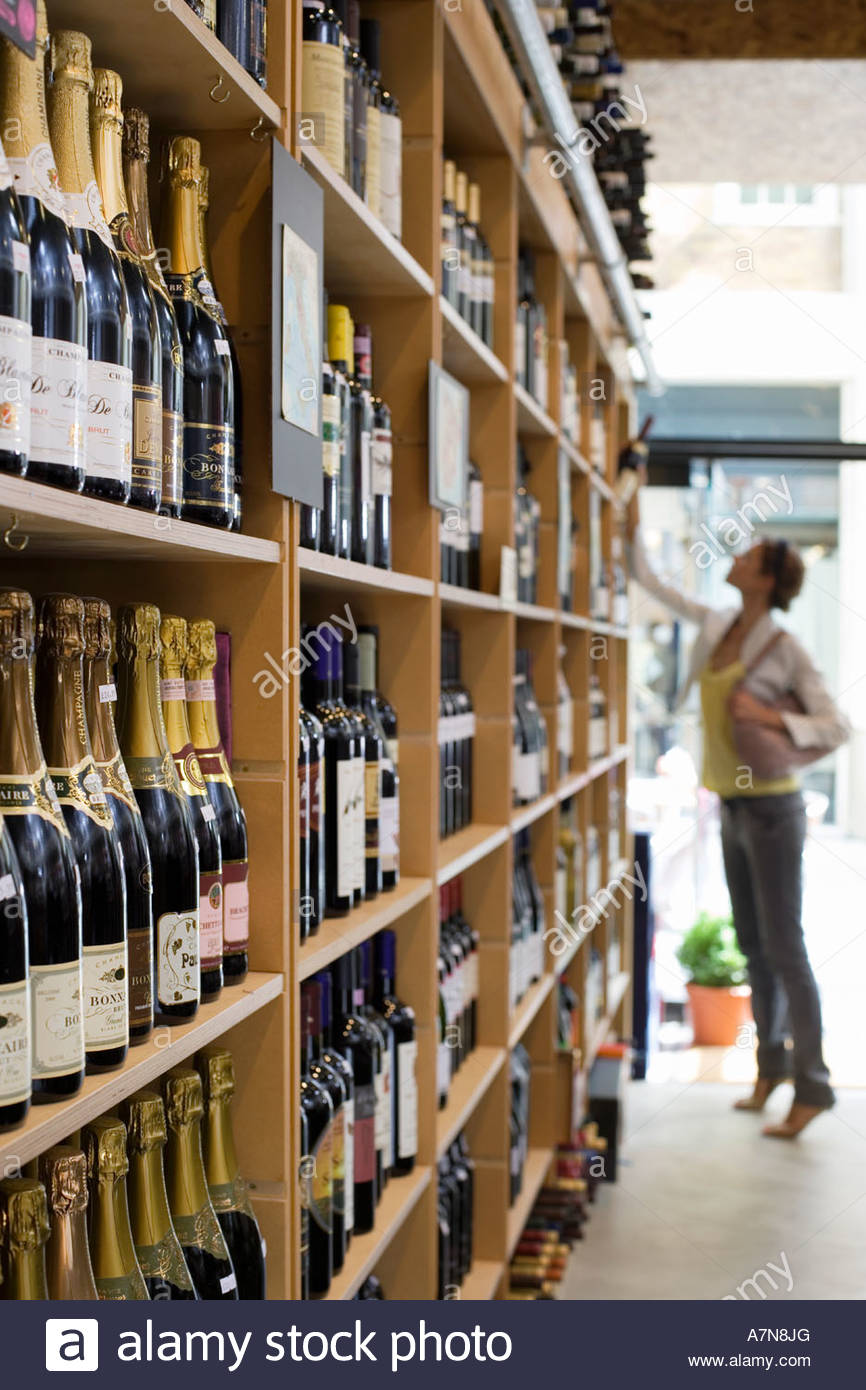 Female customer shopping in off licence looking at bottles of wine on shelf tip toeing profile - Stock Image
