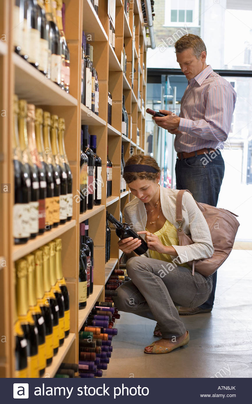 Customers shopping in off licence looking at bottles of wine on shelf woman crouching side view - Stock Image