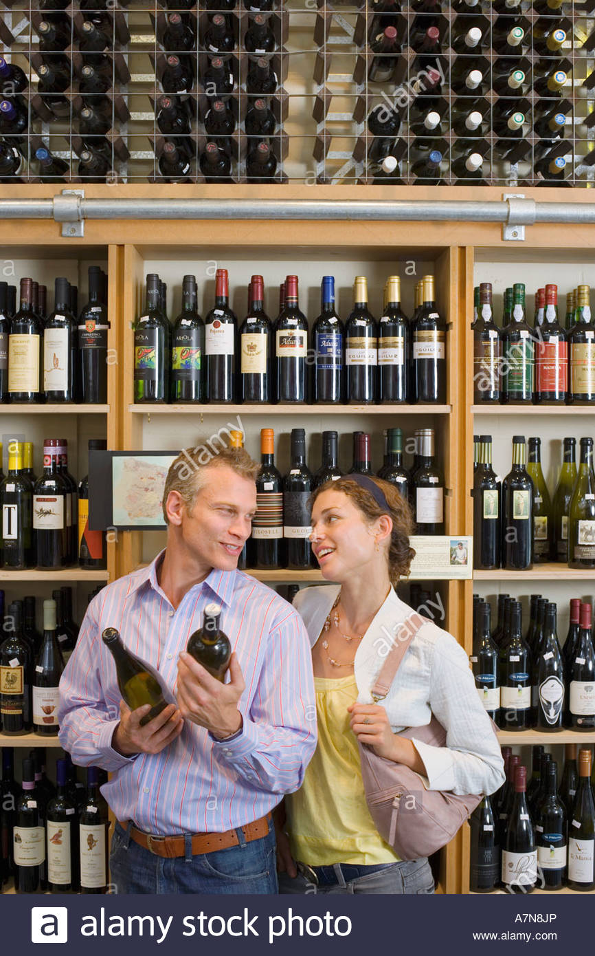 Couple shopping in off licence man holding bottles of wine smiling shelf display in background - Stock Image