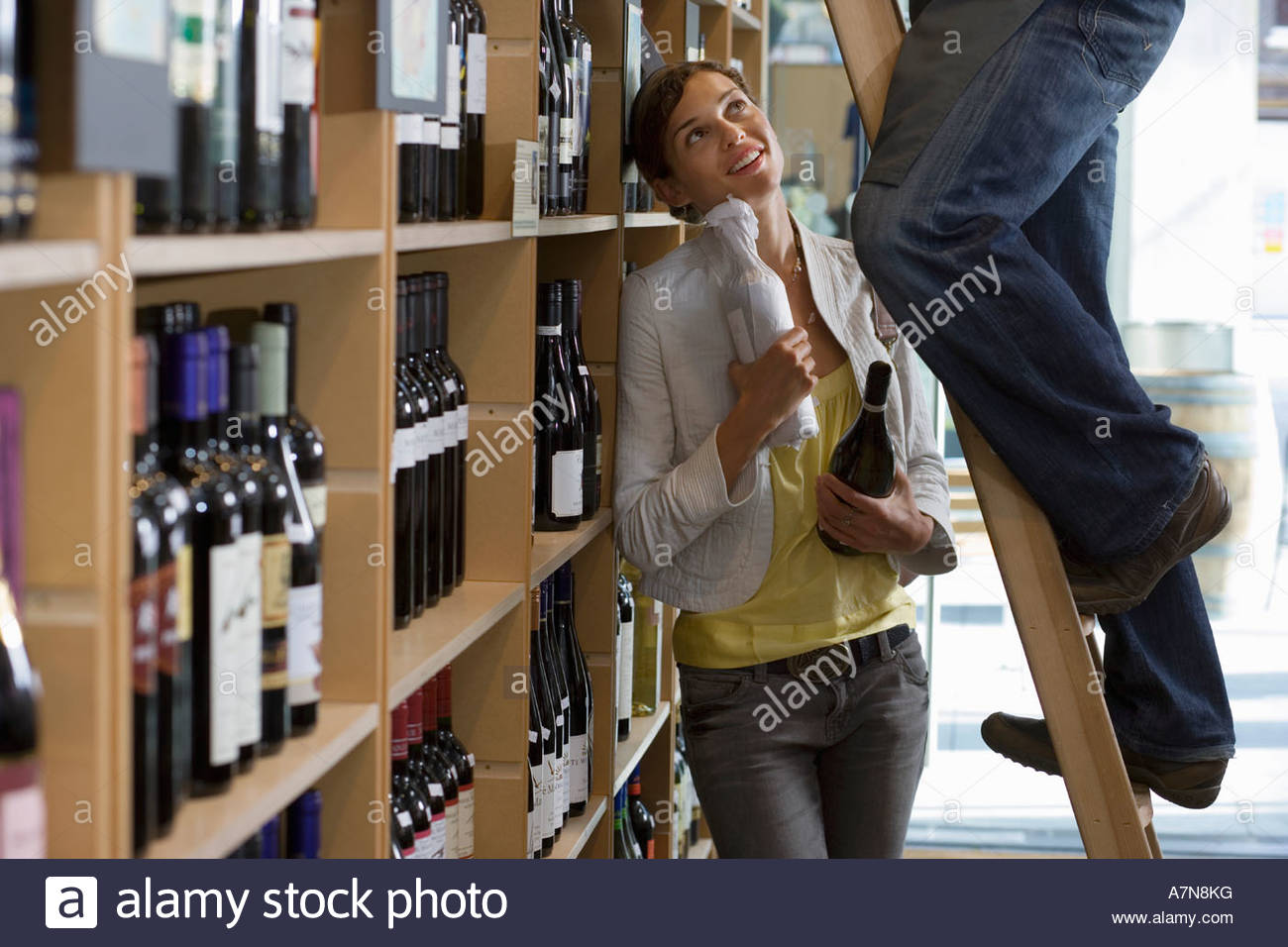 Customer talking to shop owner in off licence man standing on step ladder woman holding bottles - Stock Image