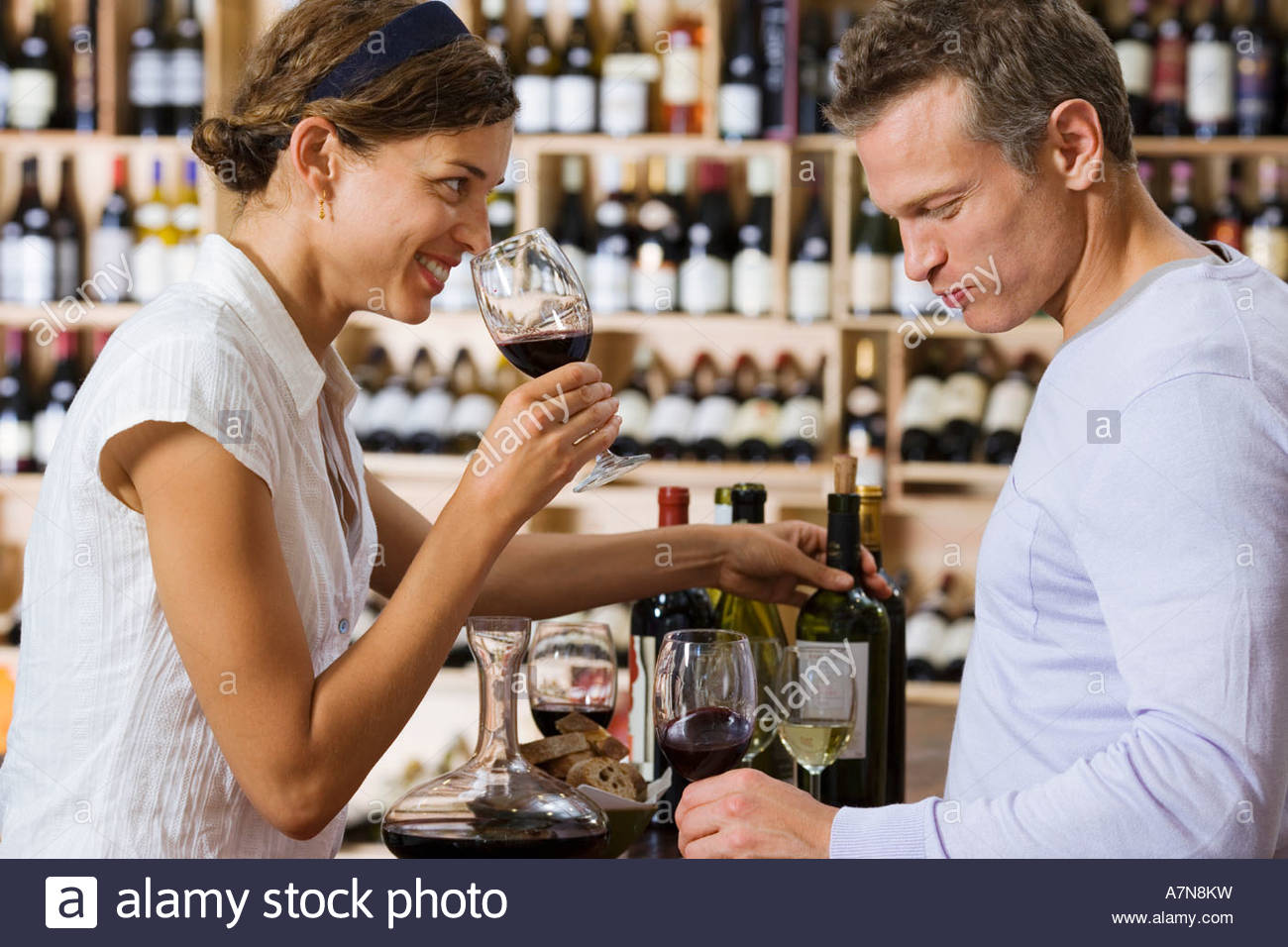 Couple wine tasting in off licence woman smelling glass of red wine man drinking profile smiling - Stock Image