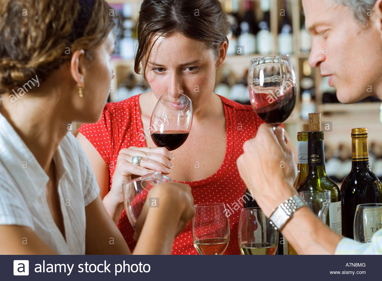 Friends wine tasting in off licence woman smelling glass of red wine differential focus - Stock Image