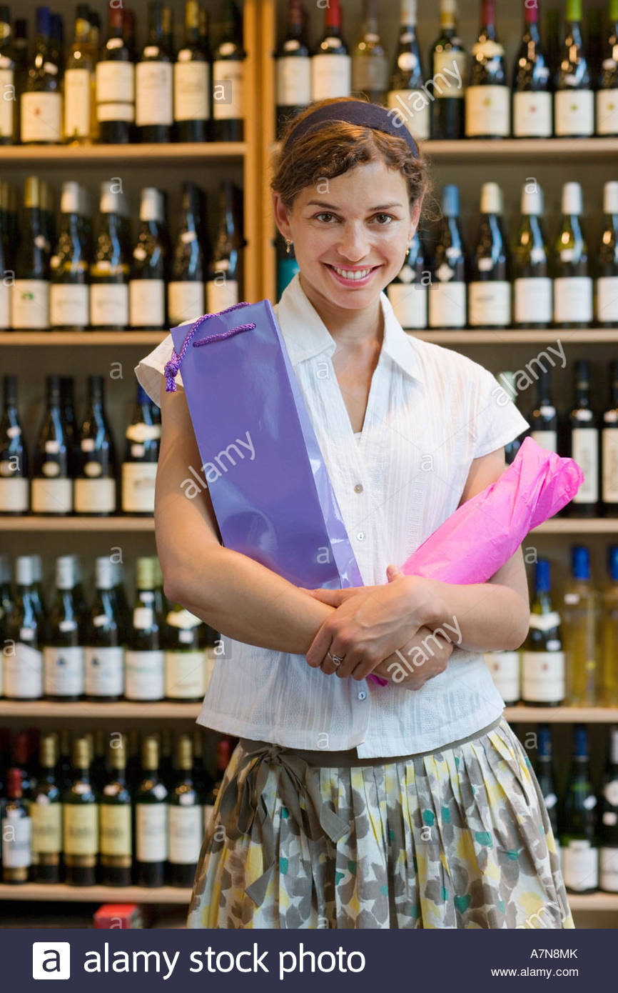 Woman standing with bottles of wine wrapped in tissue paper in off licence smiling portrait - Stock Image