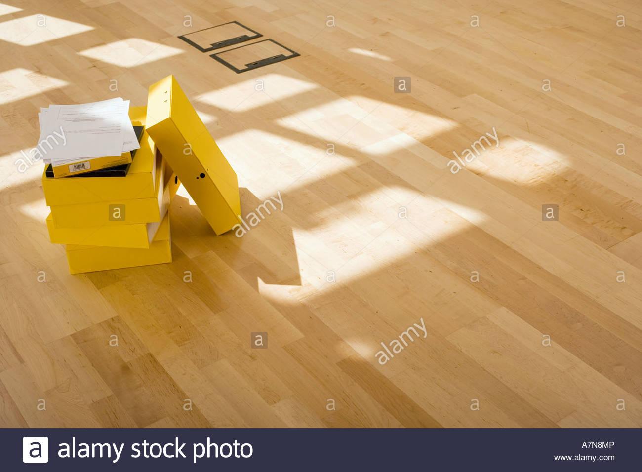Documents on stack of yellow folders on office floor sunlight shining through window - Stock Image