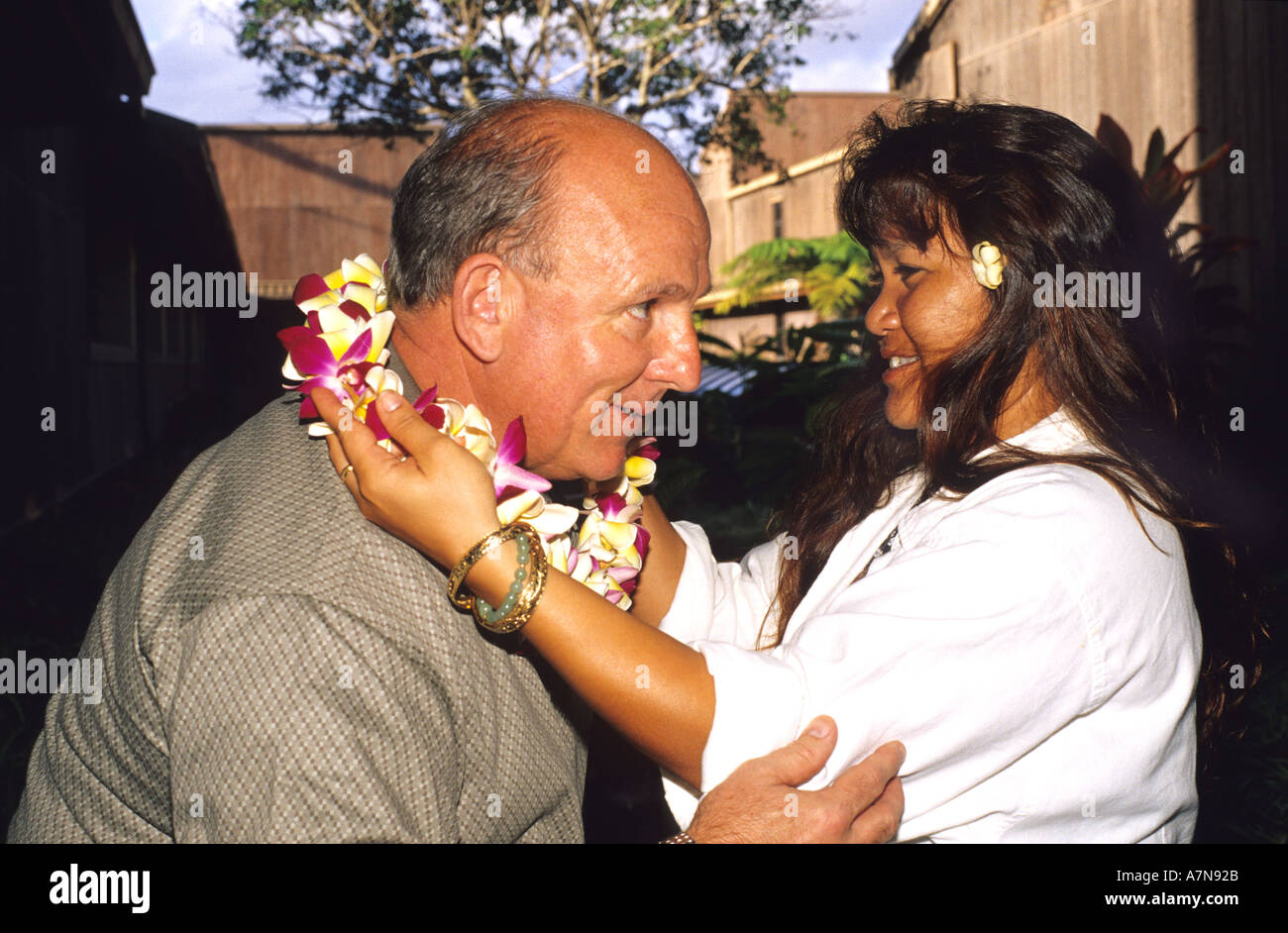 Hawaiian woman offering a lei to a tourist  - Stock Image
