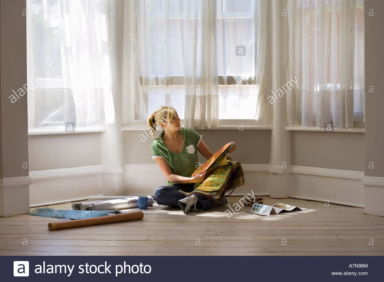 Woman decorating at home sitting on floor beside window holding ...