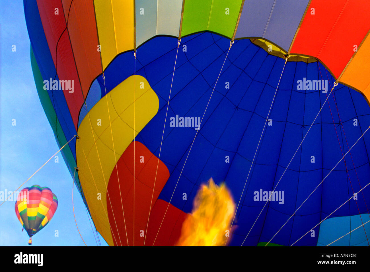 Close up of a hot air balloon heated by a propane burner in preparation for flight Another balloon rises in the background - Stock Image