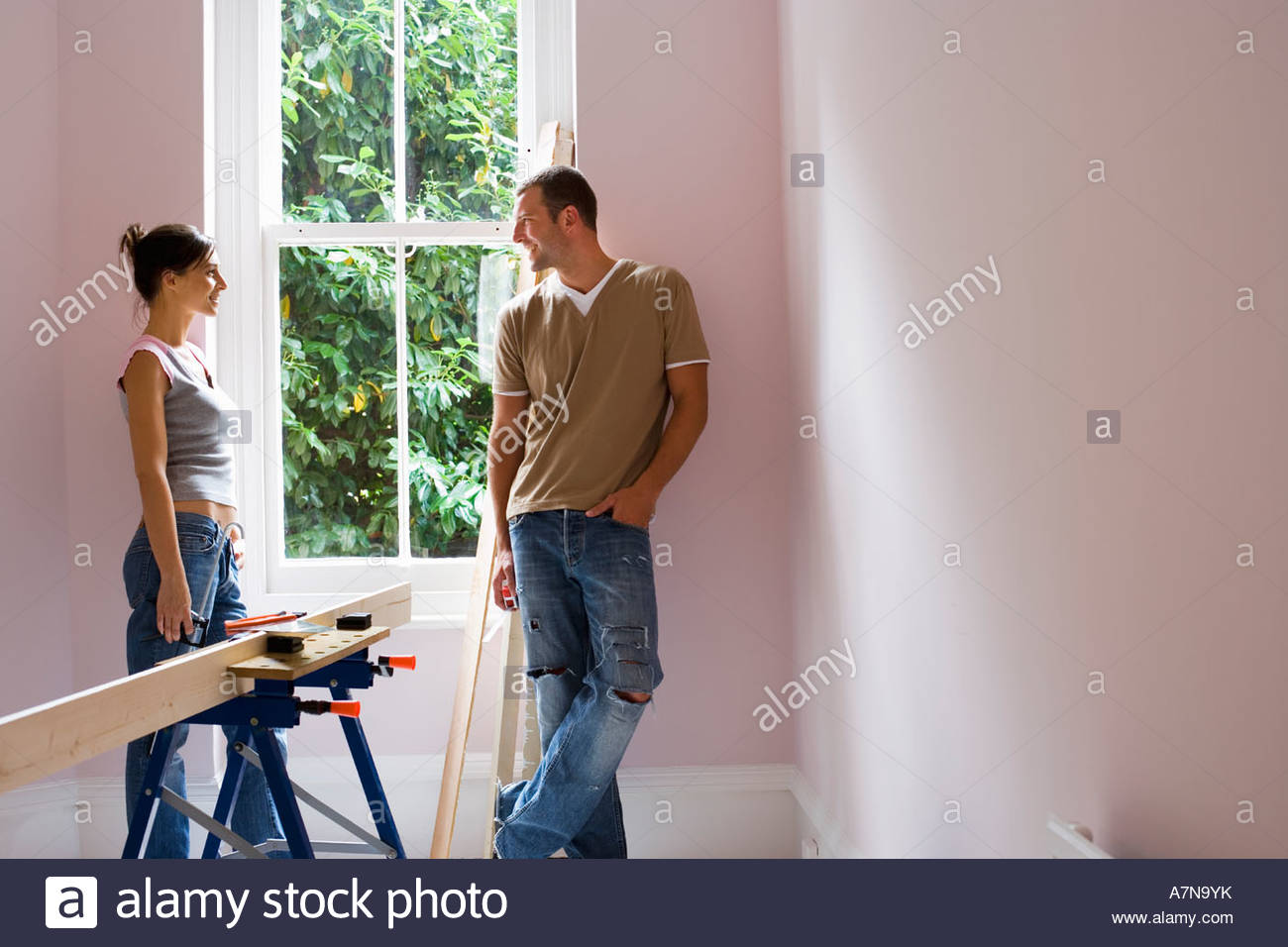 Couple doing DIY at home standing beside window woman holding glue gun near timber on workbench Stock Photo