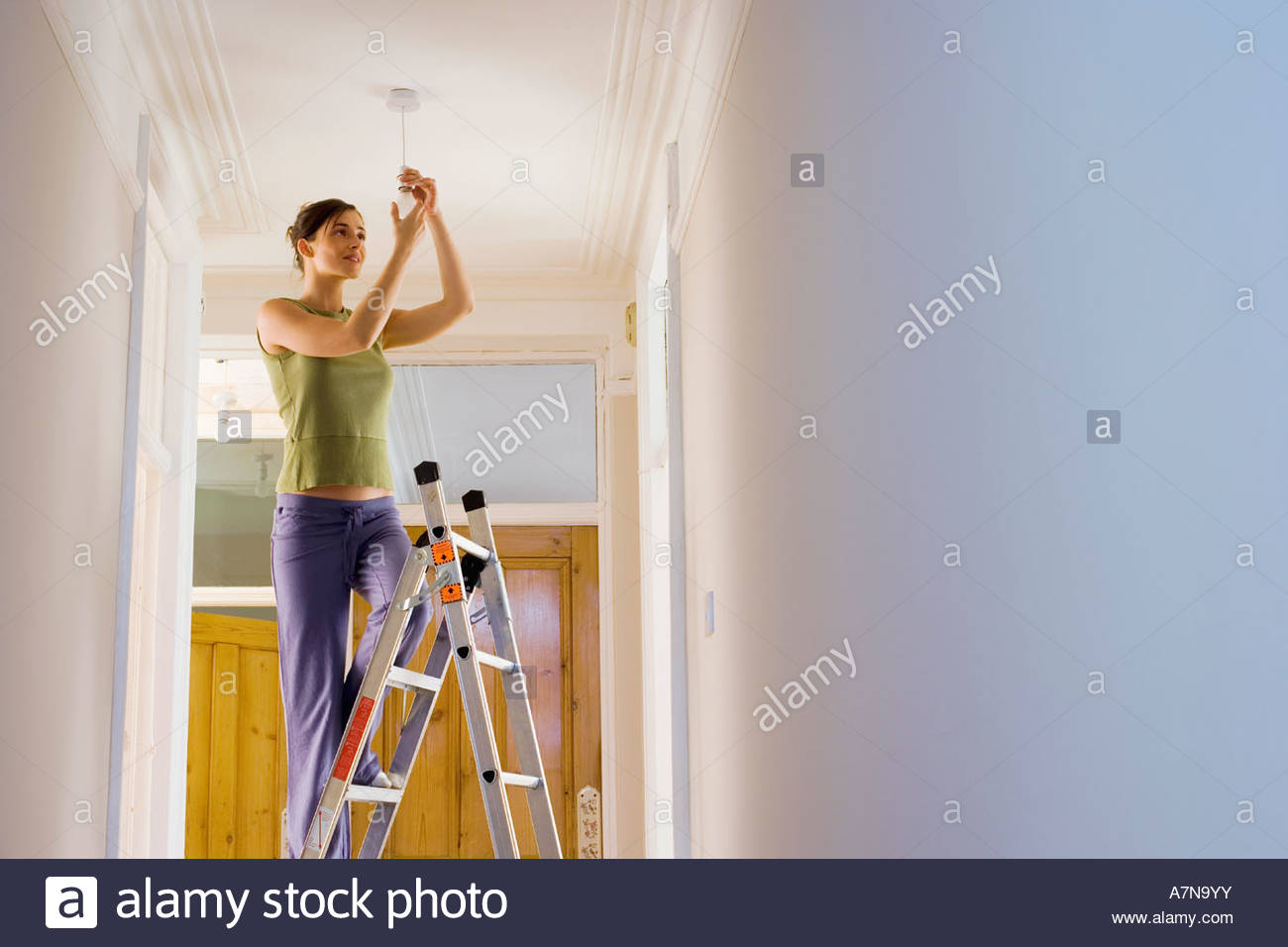 Woman doing DIY at home standing on step ladder attaching light bulb to ceiling fixture smiling - Stock Image
