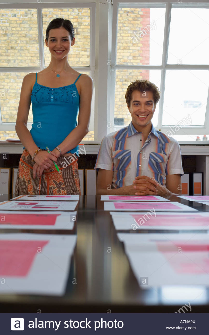 Young man and woman looking at various designs arranged on large table in office surface level - Stock Image