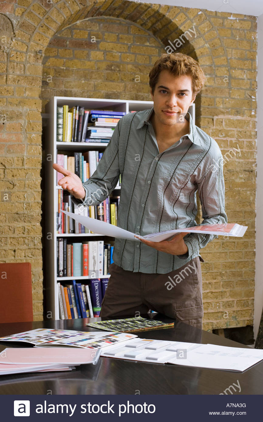 Young man looking at designs in office gesturing portrait - Stock Image