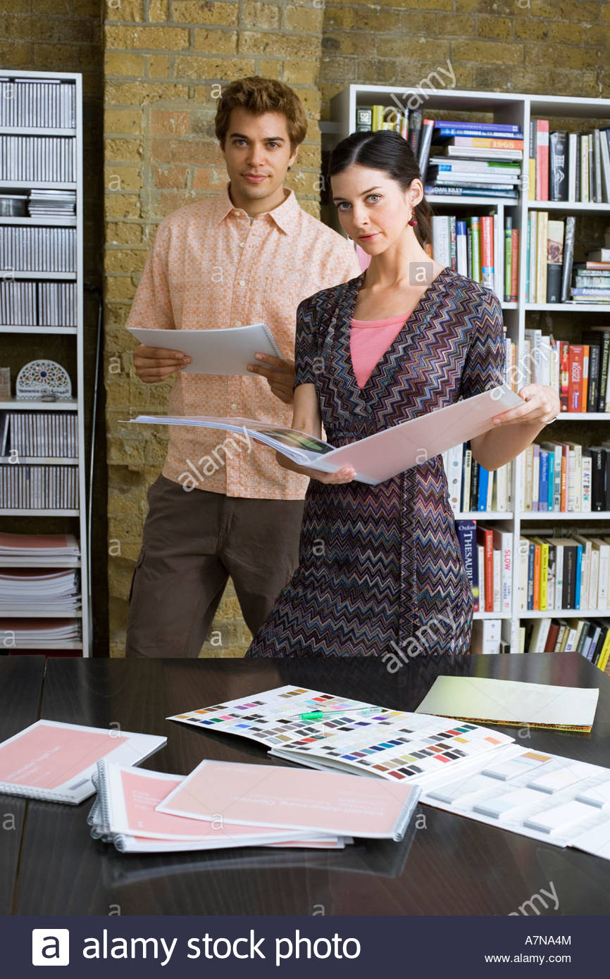 Young man and woman standing in office looking at designs in folder portrait - Stock Image