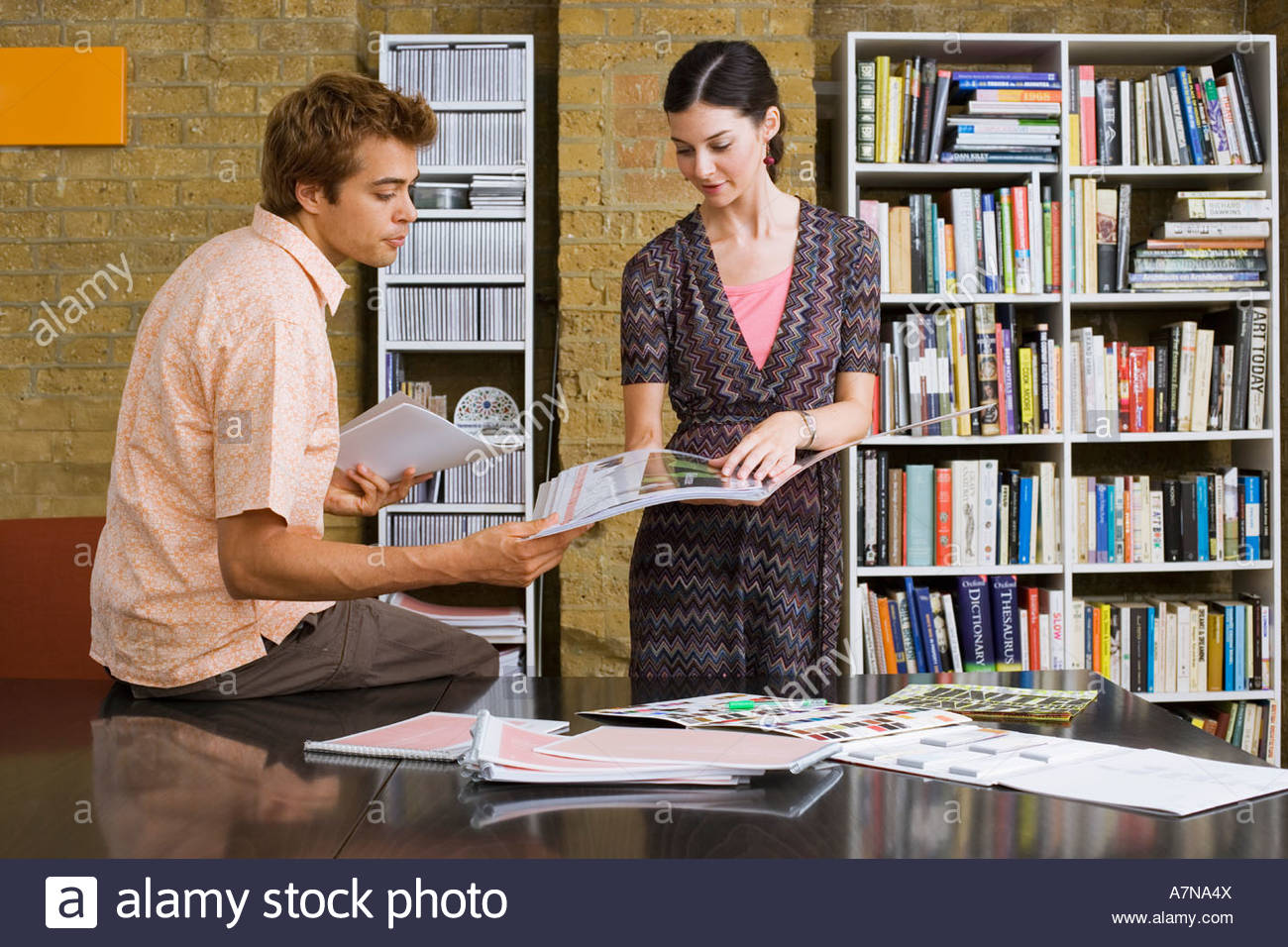 Young man and woman standing in office looking at designs in folder man leaning on desk side view - Stock Image