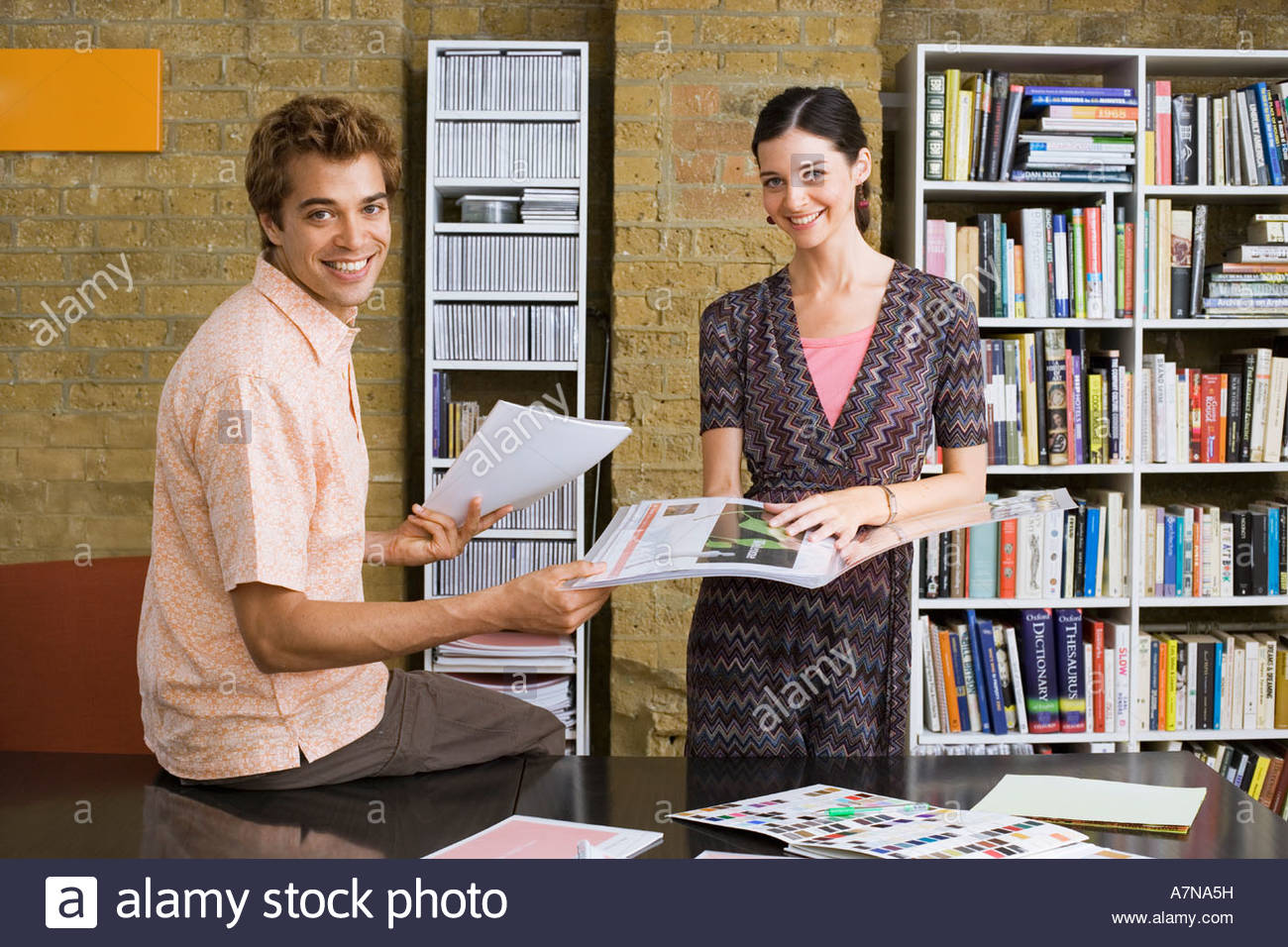 Young man and woman standing in office looking at designs in folder smiling portrait - Stock Image