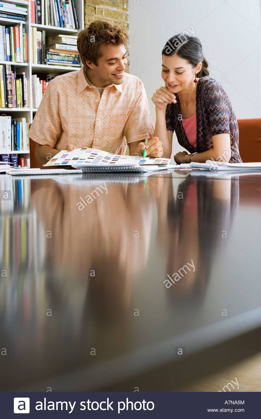 Young man and woman looking at designs on desk in office smiling surface level - Stock Image