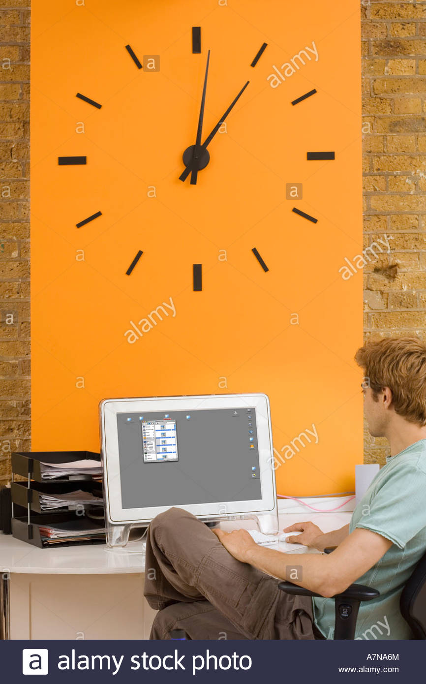 Young man sitting at desk in office beside large orange wall clock