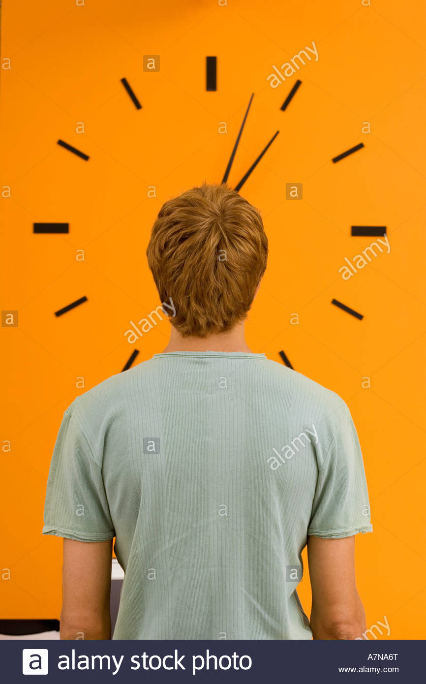 Young man staring at large orange wall clock rear view - Stock Image