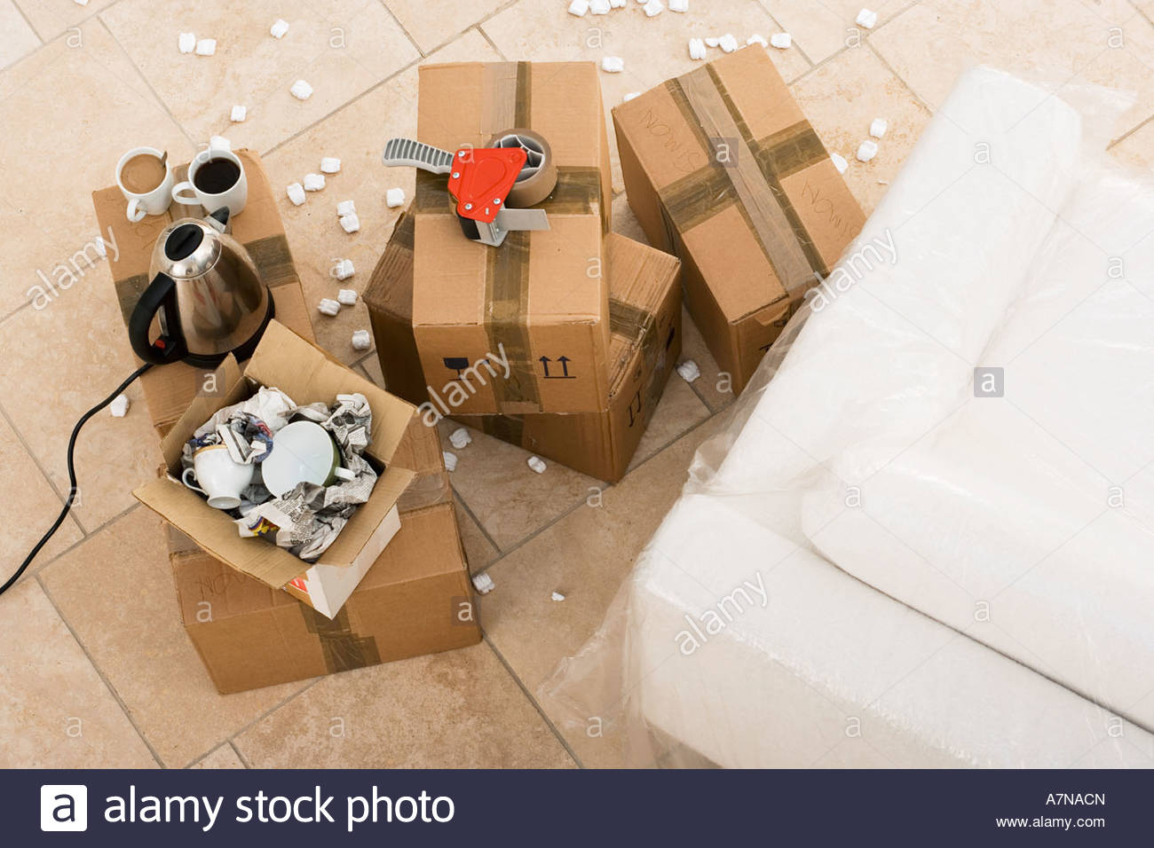Duct tape boxes crockery kettle and cups beside sofa wrapped in plastic sheet overhead view Stock Photo