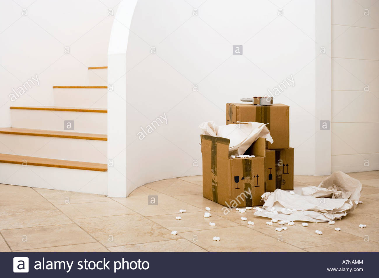 Small stack of boxes paper and packing foam beside staircase in sparse room - Stock Image