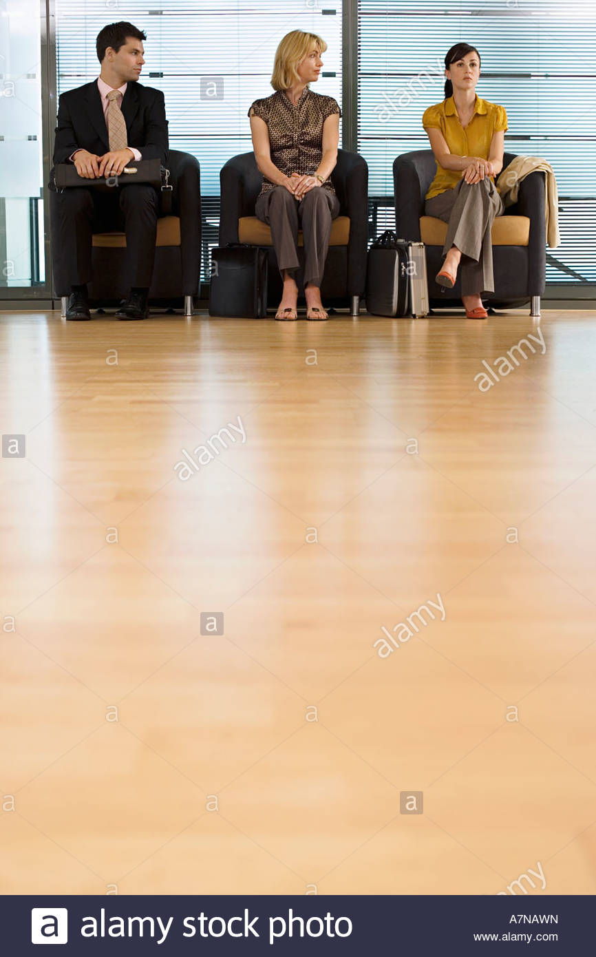 Businessman and two businesswomen sitting in office reception area front view surface level - Stock Image