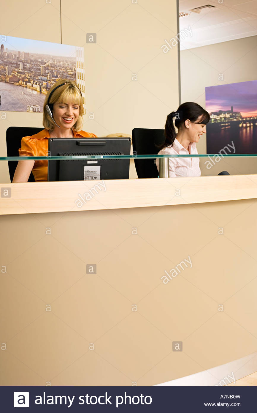 Two receptionists wearing telephone headsets working at reception desk smiling - Stock Image