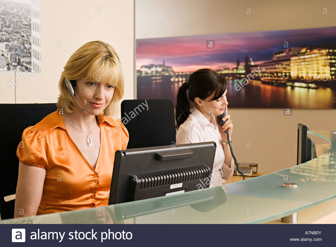 Two receptionists working at reception desk woman holding phone receiver second woman with headset - Stock Image