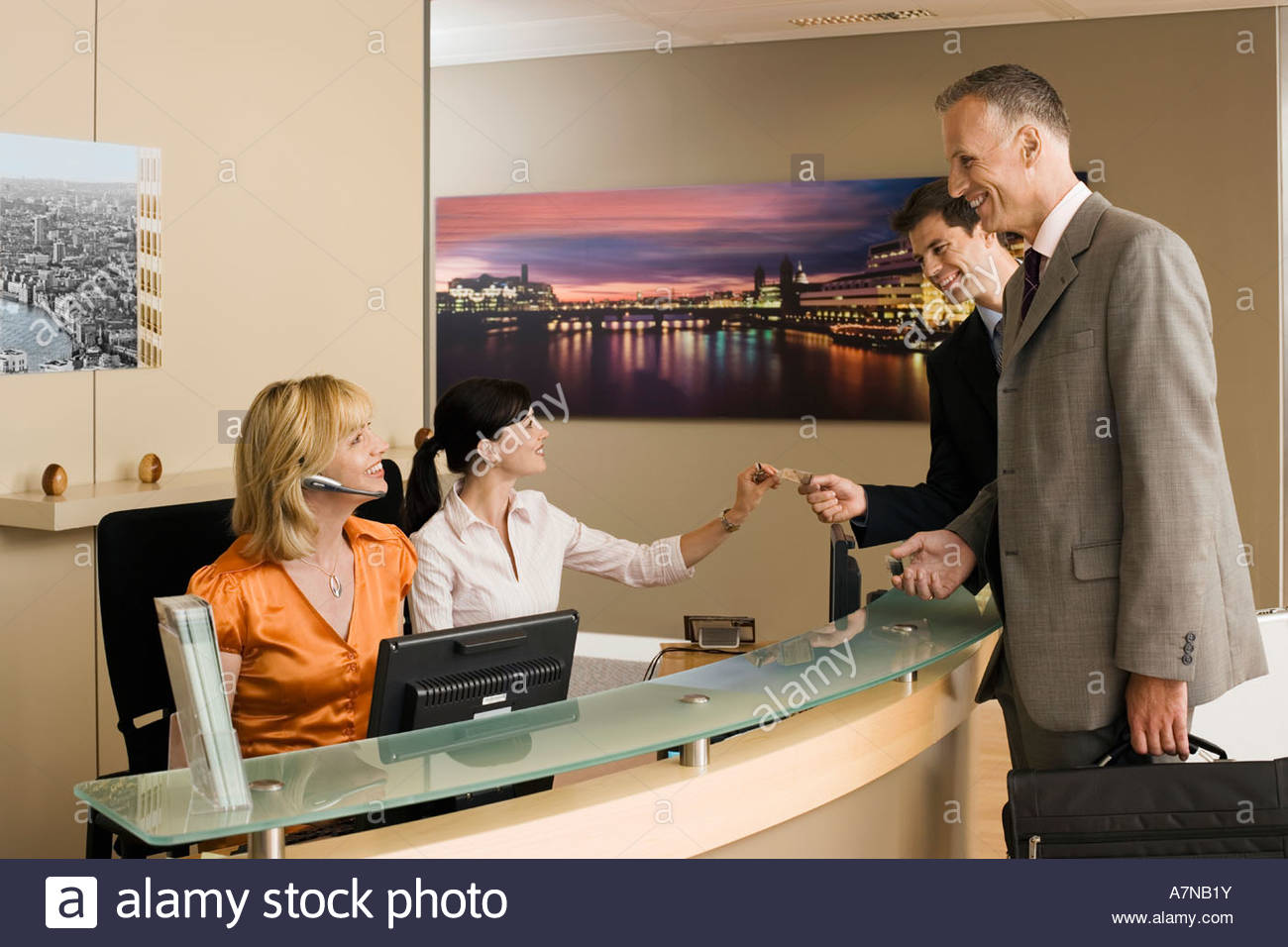 Two receptionists working behind reception desk greeting two businessmen smiling side view - Stock Image