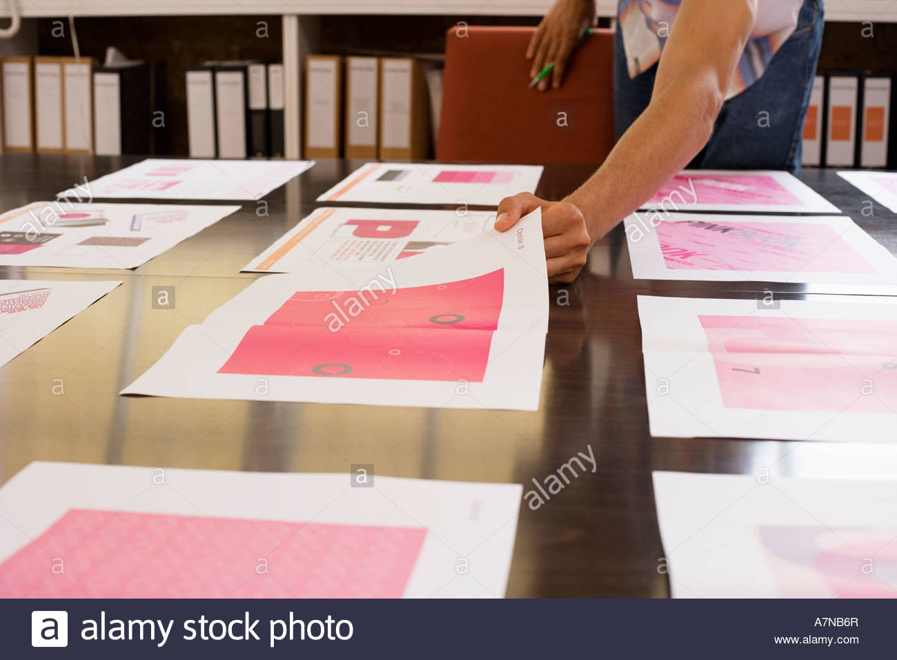 Man looking at various designs arranged on large table in office choosing one design surface level - Stock Image