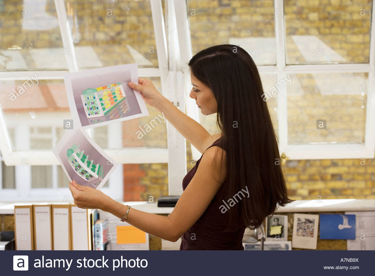 Businesswoman looking at two designs in office thinking side view - Stock Image