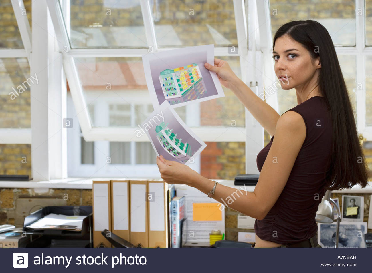 Businesswoman holding two designs in office side view portrait - Stock Image