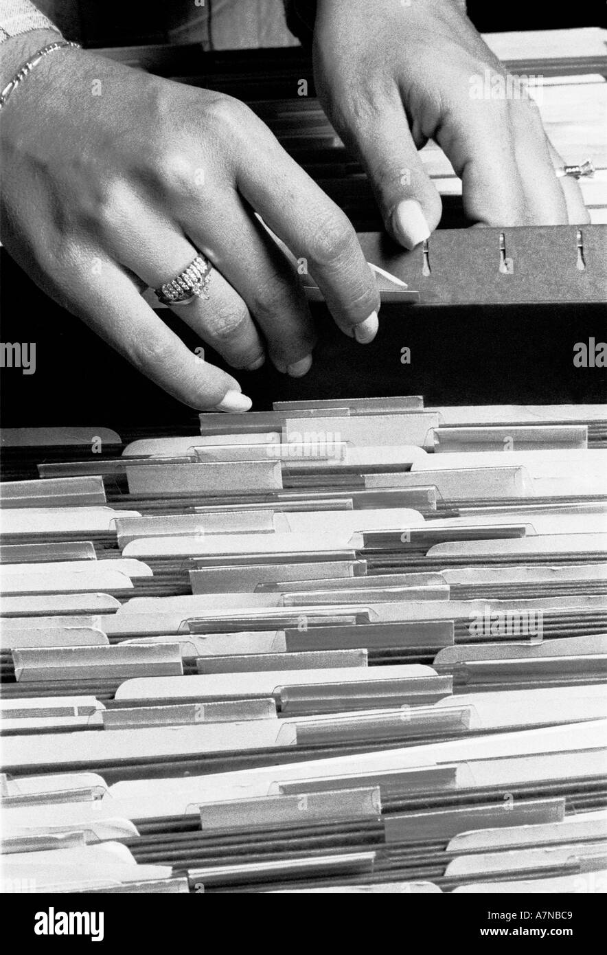 Close up of a woman hands as she looks through a drawer of hanging files - Stock Image