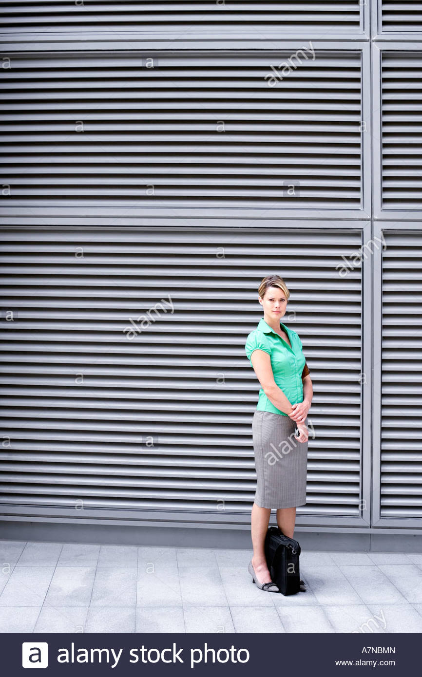 Businesswoman in green short sleeved blouse and grey skirt standing on pavement portrait - Stock Image