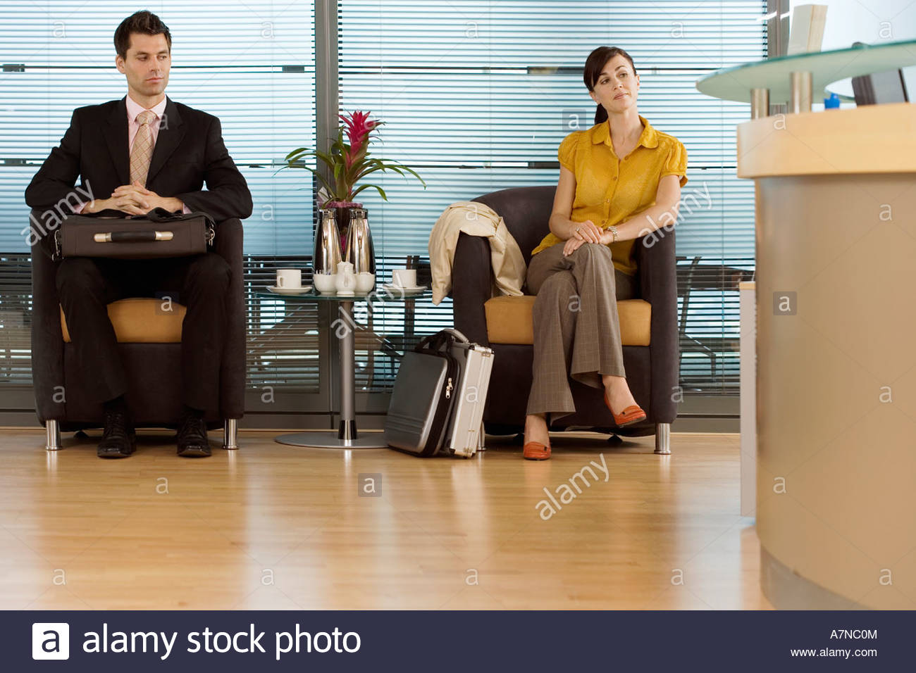 Businessman and businesswoman sitting in office reception area waiting patiently - Stock Image