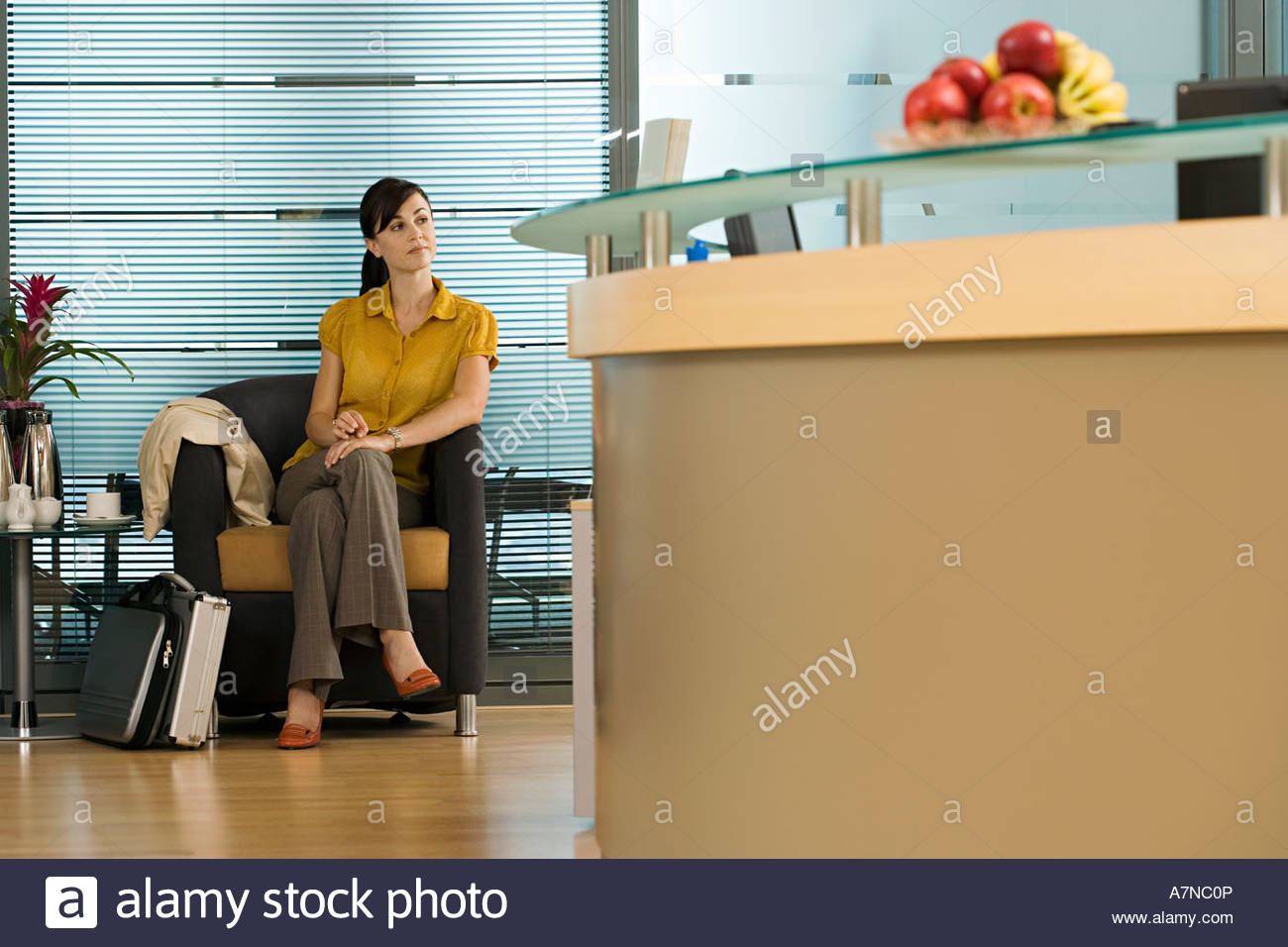 Businesswoman sitting in office reception area waiting patiently reception desk in foreground - Stock Image