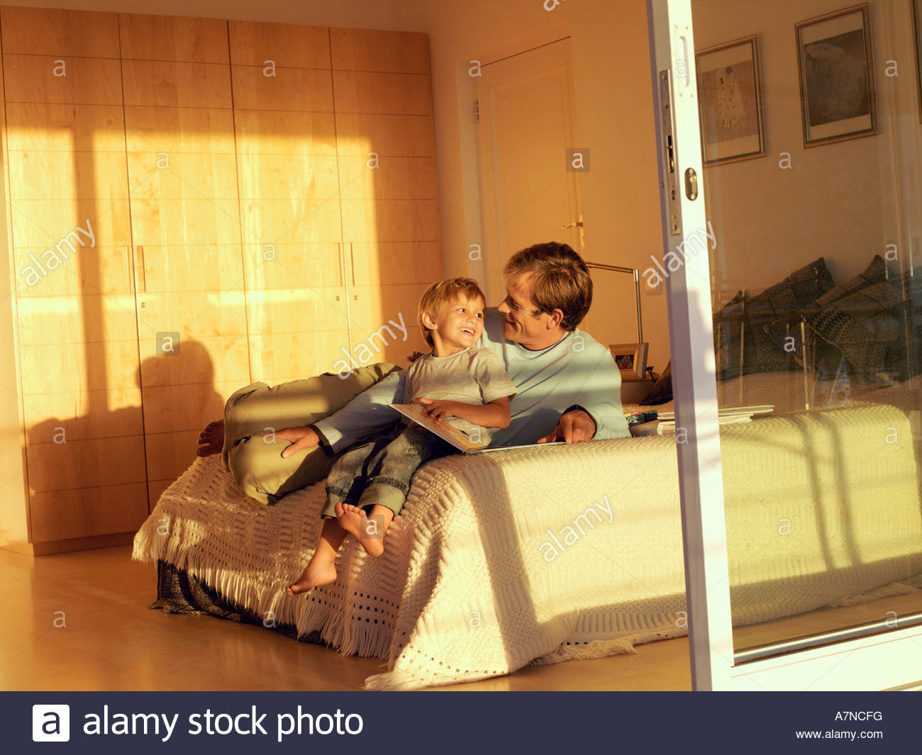 Father and son 5 7 sitting on bed looking at photo album view through open sliding doors - Stock Image