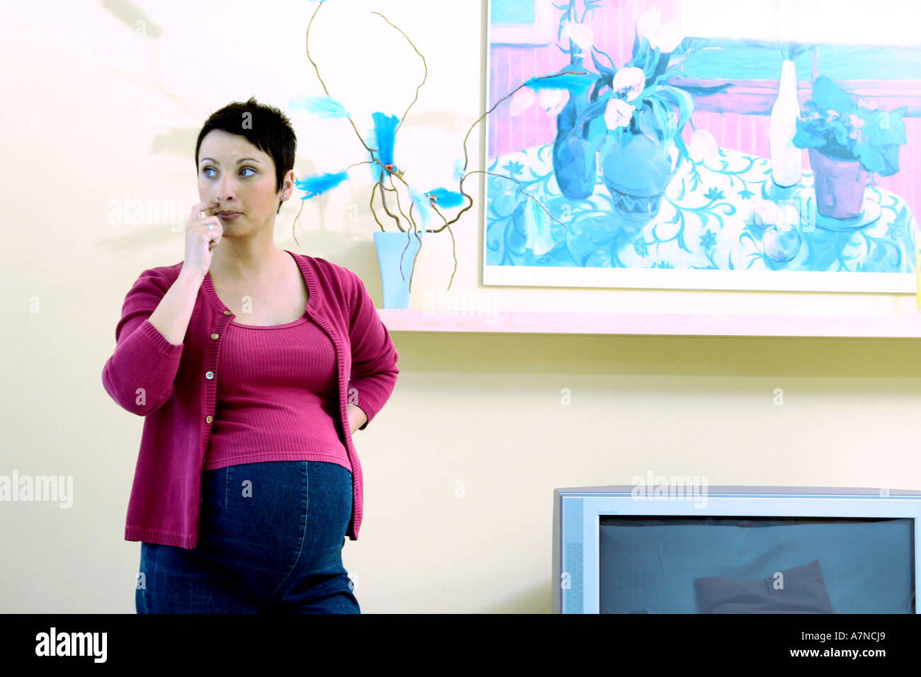 indoor flat room sittingroom woman young 25 30 brunette shirt cardigan stand stomach pregnancy pregnant think wonder wall pai - Stock Image
