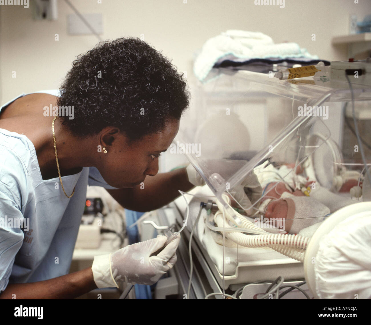 neo-natal unit in hospital with nurse attending to a baby in incubator - Stock Image