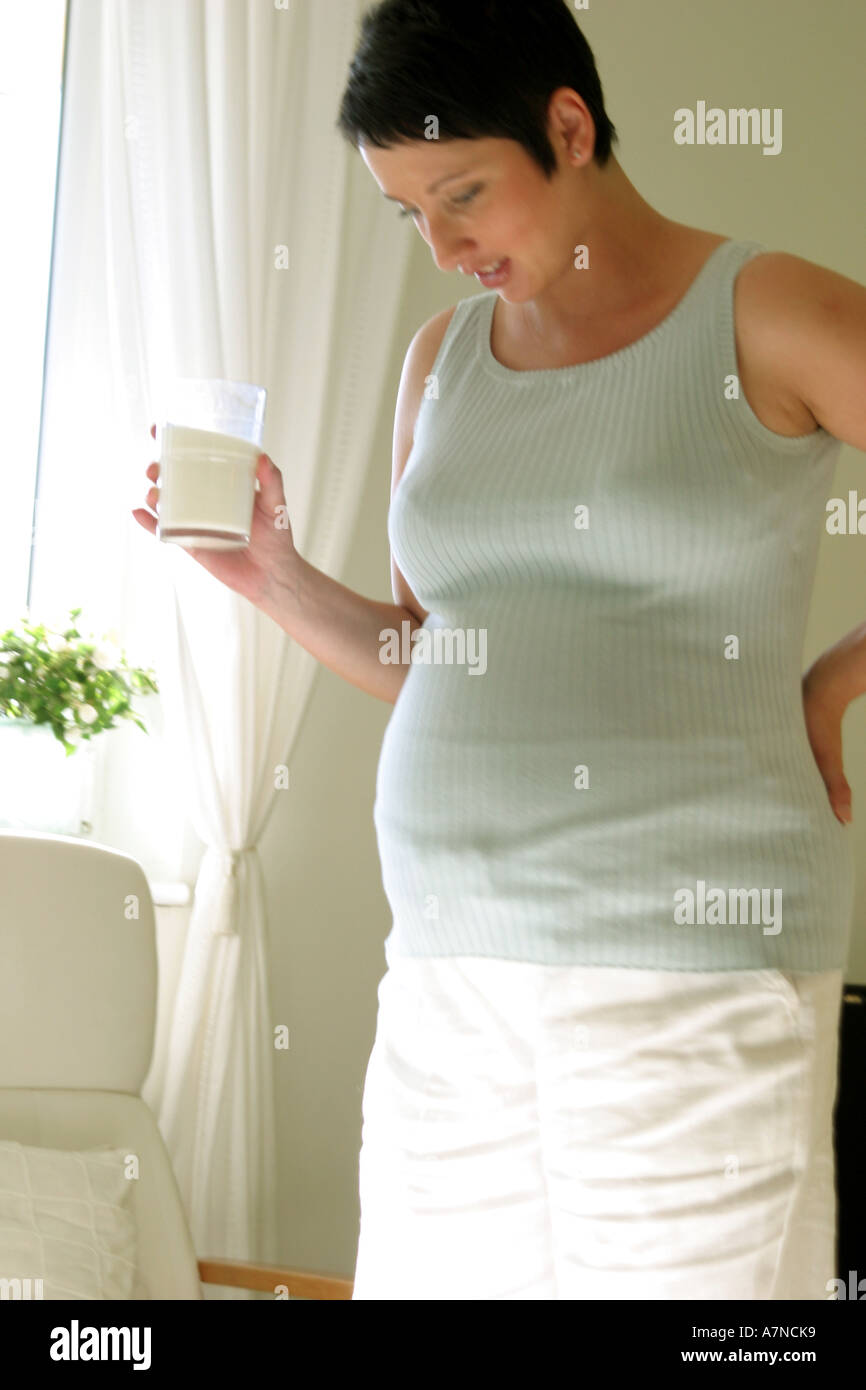 indoor flat room sittingroom woman young 25 30 brunette shirt stomach pregnancy pregnant stand hold glass milk drink armchair - Stock Image
