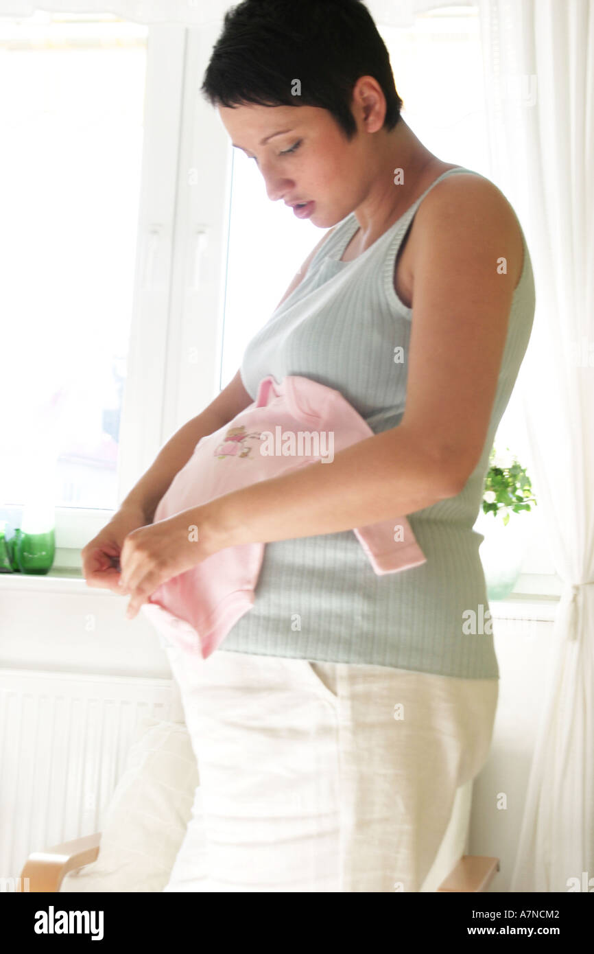 indoor flat room sittingroom woman young 25 30 brunette shirt stomach pregnancy pregnant stand hold crowler fold vertical - Stock Image